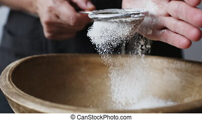Female hands sifting flour by bowl. - Slow motion shot of...