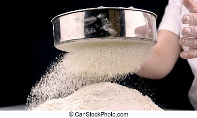 Female hands sifting flour - Closeup of female hands sifting...