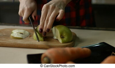 Female hands slicing apple on cutting board