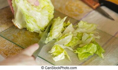 slicing iceberg lettuce - Female hands slicing iceberg...