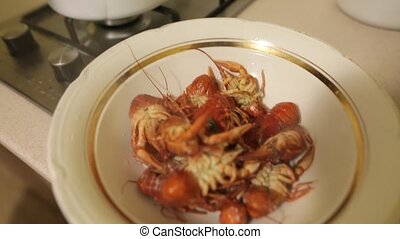 Female hands spread out a plate of red boiled crawfish. Fresh sea food cooked at home is ready to eat. Dinner on vacation.