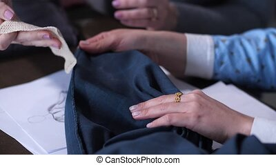 Female hands touching fabric and decor for dress - Close-up...