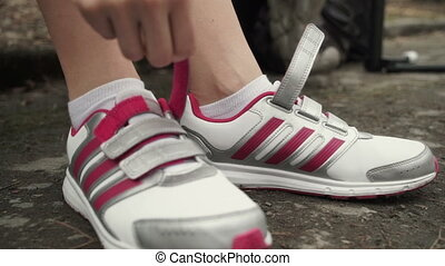 Female hands tying shoelace on running shoes before practice.