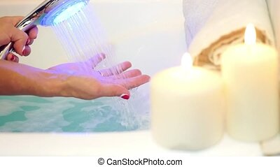 Female hands under the stream of water from shower with blue light on burning candles background. Skin care concept.