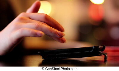 Female hands using a smartphone in cafe