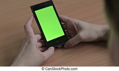 Female hands using cell phone, green screen