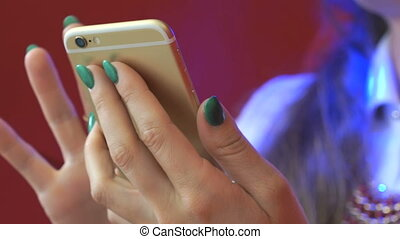Female hands using gold smartphone. Close-up
