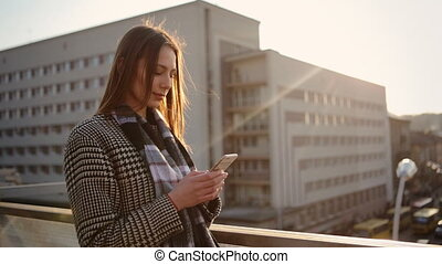 Female hands using mobile phone on the balcony of her office.