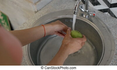 Female hands washing two delicious green apples in the water...