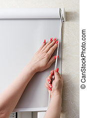 Female hands whith manicure close rolling shutters and...
