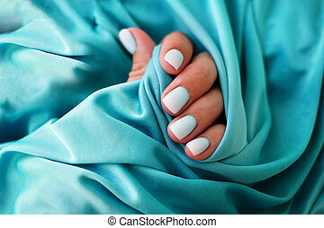 Female hands with a beautiful manicure on a blue background.