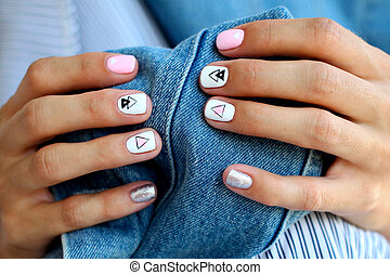 Female hands with a beautiful manicure on a jeans background.