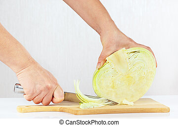 Female hands with a knife shred cabbage on a cutting board