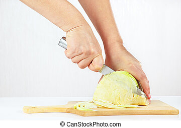 Female hands with a knife shred cabbage on a wooden cutting board