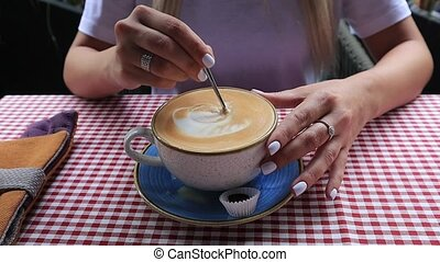 female hands with a spoon stirs sugar in coffee.