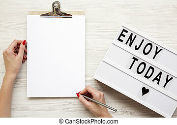 Female hands with an empty noticepad and 'Enjoy today' word on lightbox over white wooden background, top view. From above, flat lay, overhead.