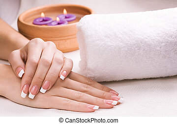 female hands with aromatic candles and towel. Spa