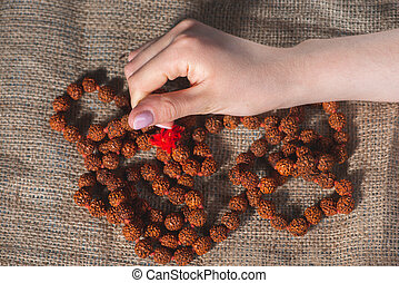 Female hands with beads on burlap