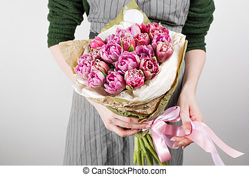 Female hands with beautiful bouquet of tulips on white wall background. Girl in a gray apron