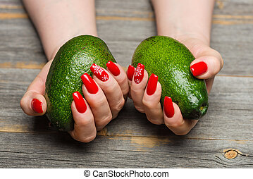 Female hands with beautiful New Year's manicure keep avocado...