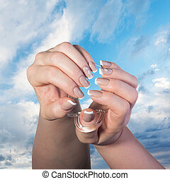 Female hands with classical French manicure hold a glass cup...