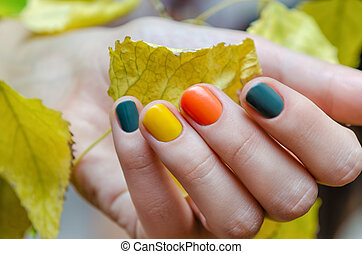 Female hands with colored fall nail design. - Female hand...