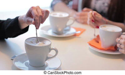 Female hands with cup of coffee in a coffee shop