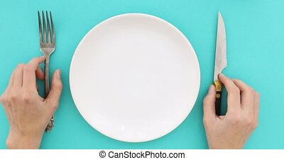 Female hands with cutlery and empty plate