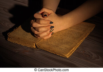 Female hands with folded hands on holy bible.