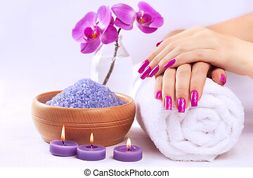 female hands with fragrant orchid and towel. Spa