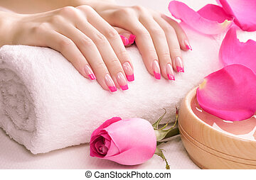 female hands with fragrant rose petals and towel. Spa - ...