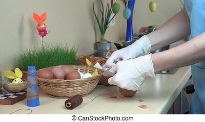 Female hands with gloves put onion shell and white egg into...