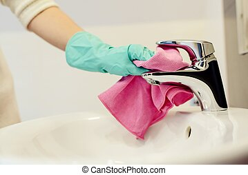 Female hands with green rubber protective gloves cleaning...