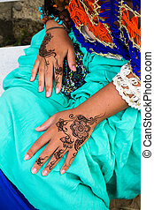 Female hands with henna tattoo mehndi on bright blue dress