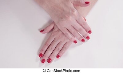 Female hands with manicure and red lacquer on a white table in the beauty salon. closeup of hand of a young woman.
