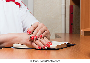 Female hands with manicure over pages of a notebook hold a...