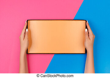 Female hands with open empty box on blue and pink background