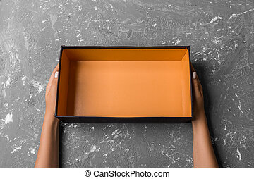 Female hands with open empty box on gray background