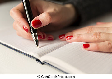 Female hands with pen writing on notebook. Diary, plans, journalist