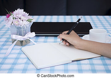 female hands with pencil writing on notebook with laptop and flower vase.