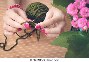 Female hands with purple manicure are knitted metal spokes of a wooden table
