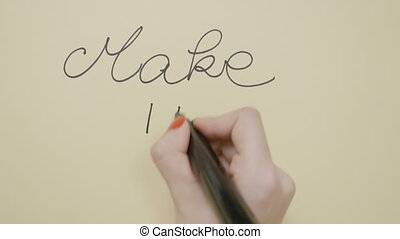 Female hands with red manicure writing inspirational quote make it possible on a blank paper using a black marker