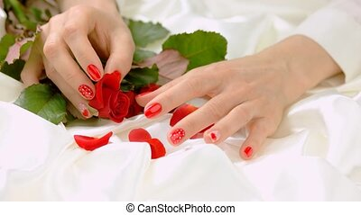 Female hands with roses on white silk. Young woman beautiful...
