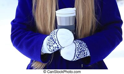 Female hands with thermal coffee mug in winter day