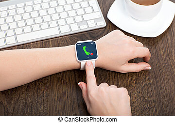 female hands with white smartwatch with phone call on the screen over a wooden table in an office