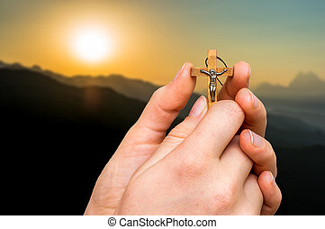 Female hands with wooden cross and sunset in the mountains