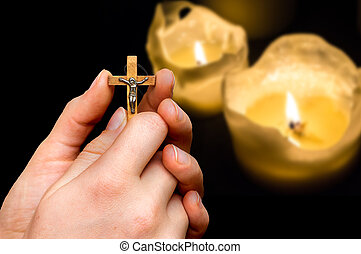 Female hands with wooden cross on candles background