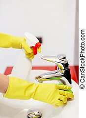 Female hands with yellow rubber gloves cleaning tap with sponge.