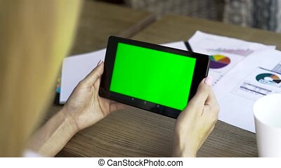 Female hands working in the office with tablet-pc, on wooden table, close-up. The display has a green screen