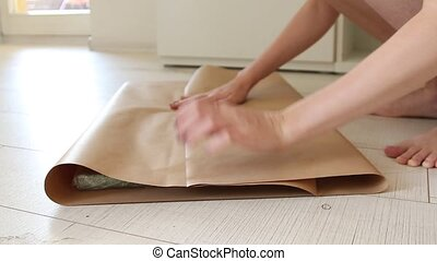 Female hands wrap a gift in craft gift paper. Preparation...
